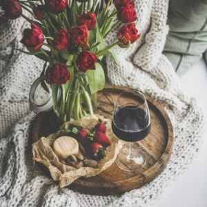 Red wine, snacks and tulips over knitted blanket, square crop