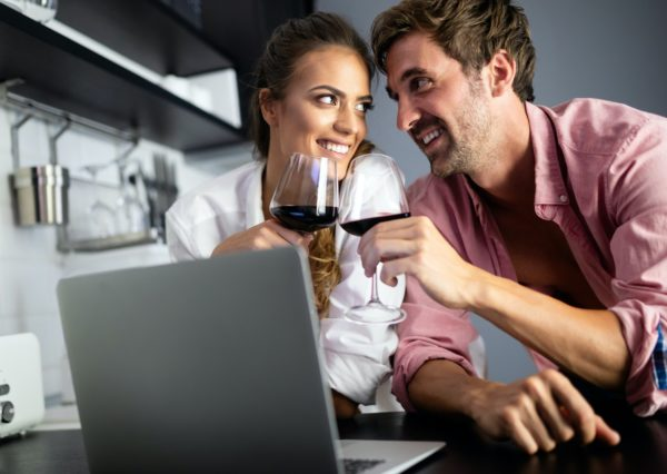 Young couple relaxing in kitchen with wine and laptop. Love, technology, people concept